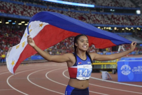 Kayla Anise Richardson of the Philippines celebrates her win in the women's 100-meter final at the SEA Games in Singapore Tuesday, June 9, 2015.(AP Photo/Joseph Nair)