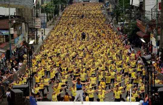 Filipino residents participate in a Zumba class in an attempt to break the Guinness World Record in Mandaluyong on July 19, 2015. Residents broke the record for the largest Zumba class with 12,975 participants in a single venue. AFP PHOTO / NOEL CELIS