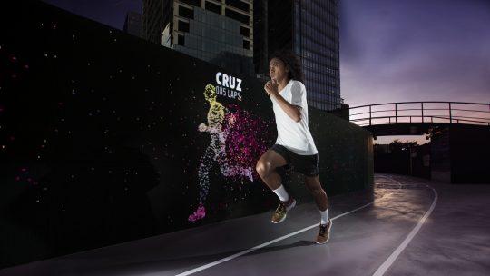 Nike Run Club Coach Rio dela Cruz outpacing his avatar at the Unlimited Stadium