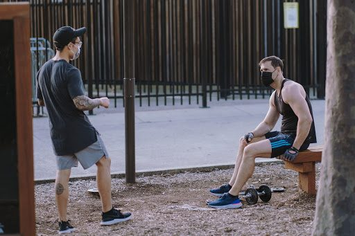 Two men wearing face masks while interacting outdoors