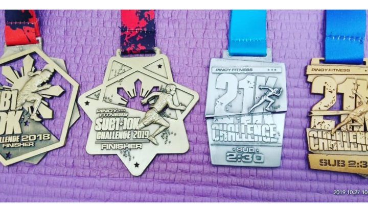 Photo of Ruby Aranas' Pinoy Fitness SUB1 10K and SUB2 21K Challenge finisher's medals